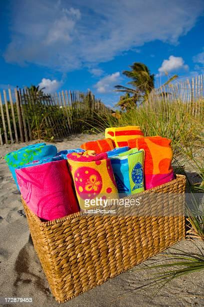 Towels in wicker basket on sand