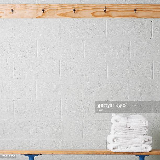 towels on a locker room bench - locker room stock pictures, royalty-free photos & images