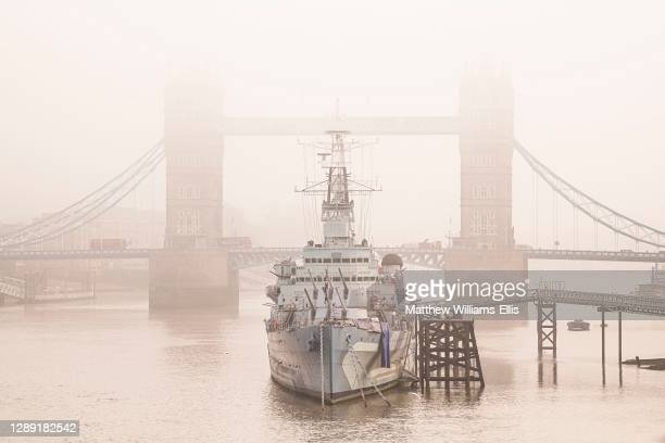 Tower Bridge and HMS Belfast in London in foggy misty weather on the River Thames in beautiful mysterious atmospheric light, shot in Coronavirus...