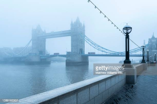 Tower Bridge and Red London Bus driving over River Thames in foggy and misty atmospheric and moody weather conditions on Coronavirus Covid-19...