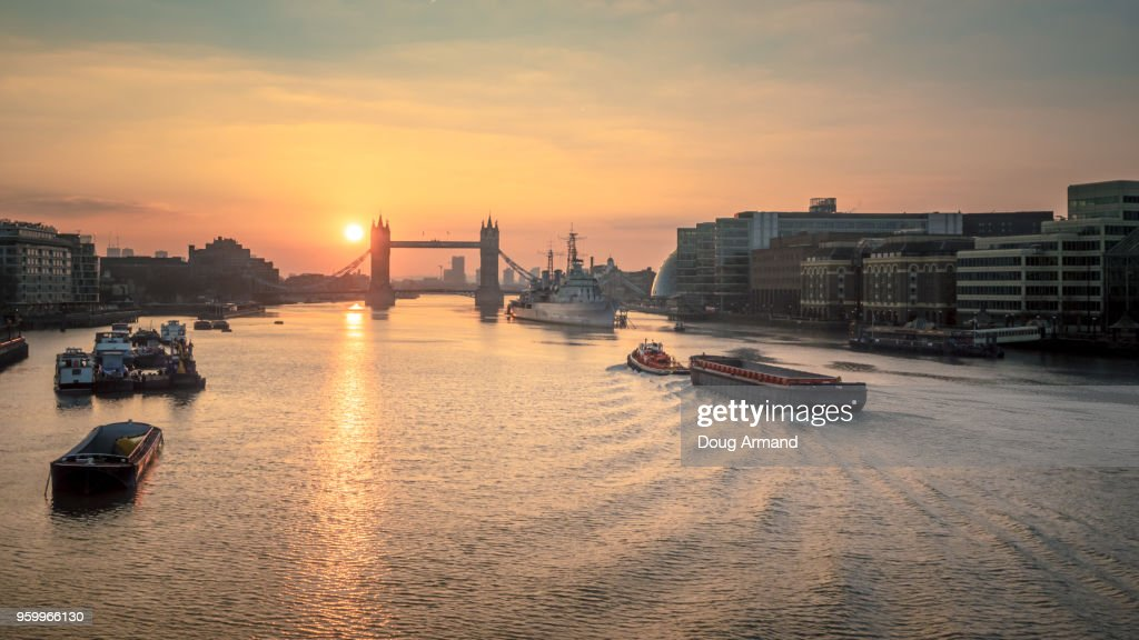 Tower Bridge at sunrise with a barge moving along the river Thames, London, UK : Stock-Foto
