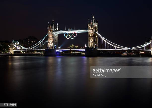Tower Bridge during the London 2012 Olympics Games and the famous Olympic rings suspended from the upper level; Canary Wharf, London second financial...