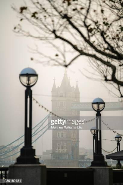 Tower Bridge, iconic London landmark in foggy and misty atmospheric moody weather in London City Centre on Coronavirus Covid-19 lockdown day one,...