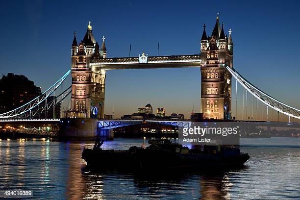 Tower Bridge illuminated at blue hour - Canary Wharf in the distance, and two silhouetted boats sit silently on the calm Thames.