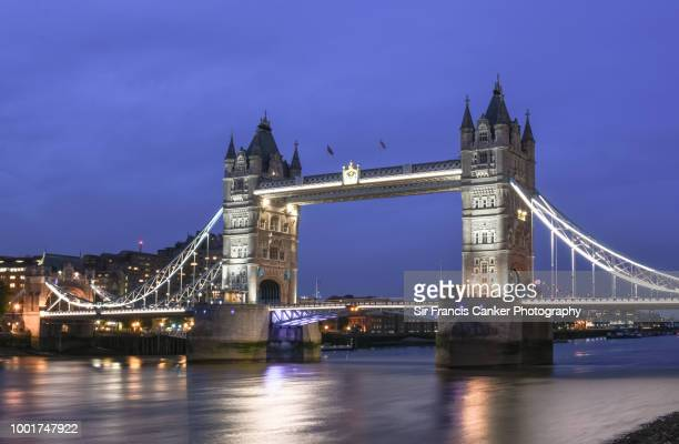 tower bridge illuminated at late dusk in london, england, uk - bandiera inglese foto e immagini stock