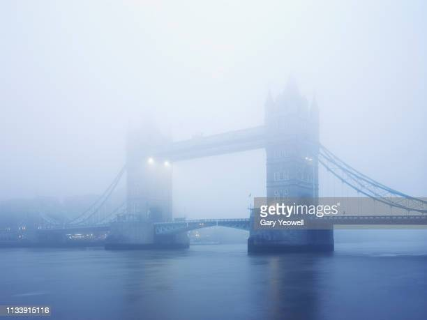 tower bridge in mist - river thames stock pictures, royalty-free photos & images