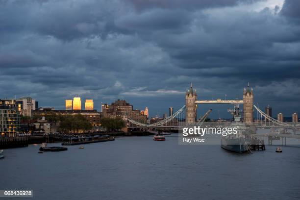 tower bridge open at sunset under moody sky. - battleship stock pictures, royalty-free photos & images