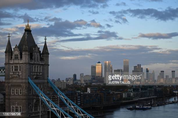 Tower Bridge over The River Thames and, in the distance, the secondary central business district of Canary Wharf are pictured as the sun sets in...