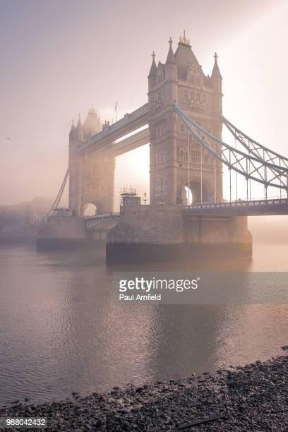 Tower Bridge over the River Thames surrounded by fog in London, England.