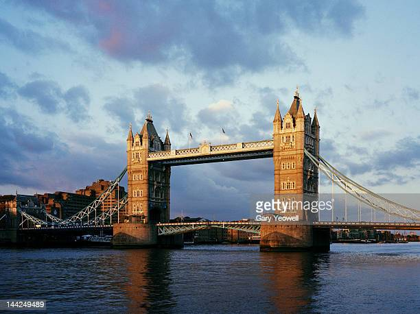tower bridge reflected in river thames at sunset - yeowell stock photos and pictures
