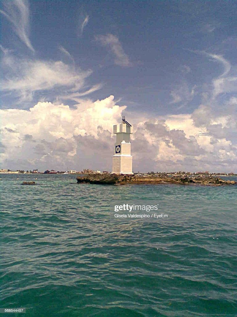Tower By Sea Against Cloudy Sky : Stock Photo