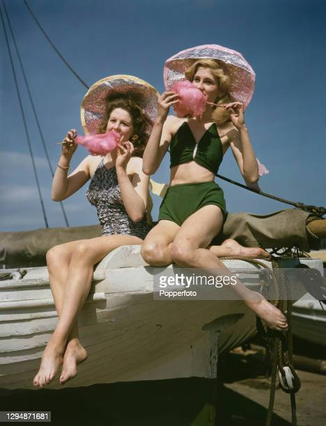 Tower Circus dancers Geraldine Ball and Valerie Purvis, dressed in swimwear, eat candy floss whilst seated on a sailing boat during a break in...