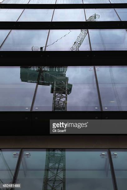 A tower crane on a building site in the City of London is reflected in the windows of an adjacent office block on November 29 2013 in London England