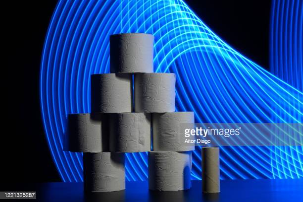 tower formed with new toilet paper rolls, there is as well an empty paper roll. modern background with curved blue lines. - hemorroide fotografías e imágenes de stock