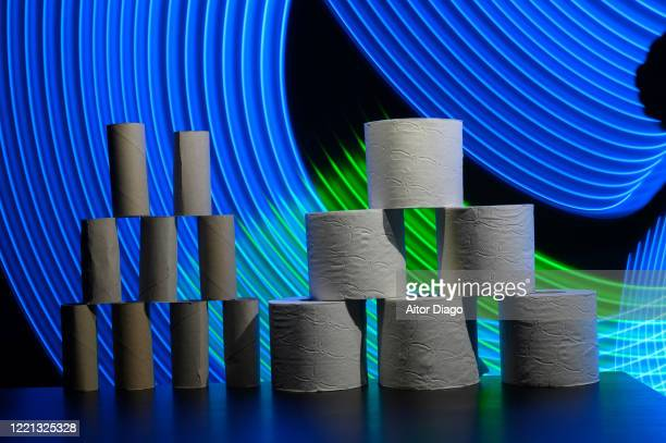 tower of empty versus full toilet paper rolls in a futuristic background with curved blue and green lines. - hemorroide fotografías e imágenes de stock
