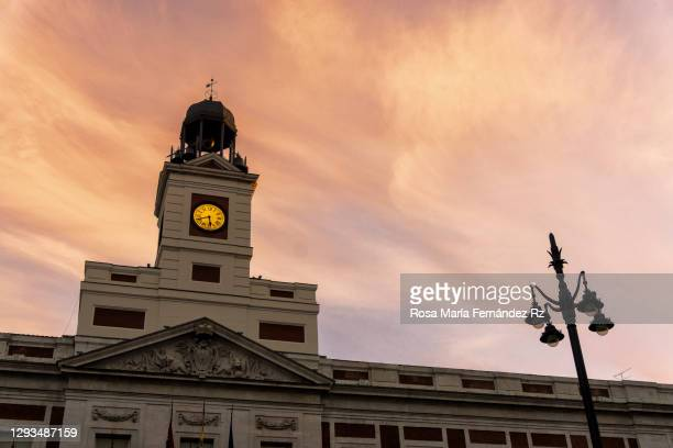 tower of the clock on la casa de correos at puerta del sol square at sunset. madrid, spain - madrid stock pictures, royalty-free photos & images