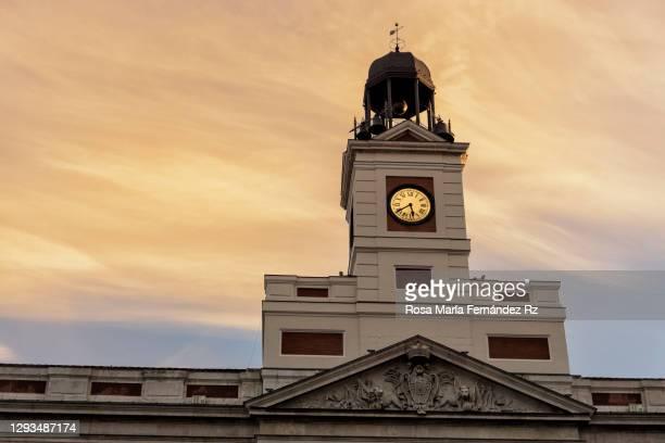 tower of the clock on la casa de correos at puerta del sol square at sunset. madrid, spain - puerta del sol fotografías e imágenes de stock