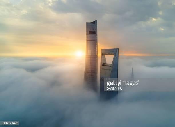 tower over the fog - wolkenkratzer stock-fotos und bilder