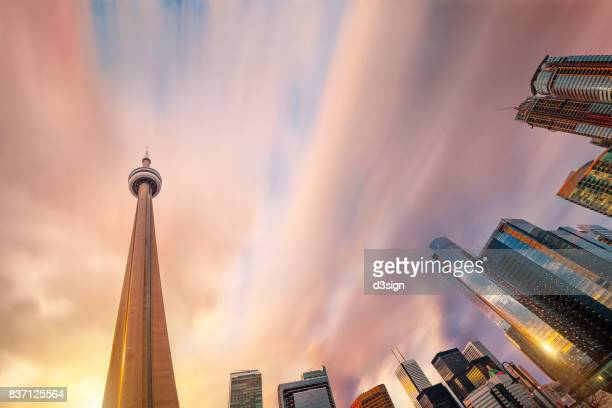 cn tower rising straight up against modern corporate skyscrapers in downtown toronto at sunset - toronto ontario canada fotografías e imágenes de stock