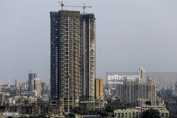 A tower stands under construction among other residential and commercial buildings in the Mahalaxmi area of Mumbai India on Monday May 11 2015...