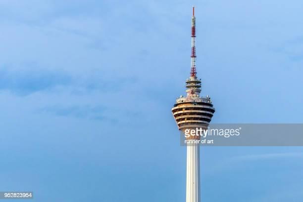 kl tower with blue sky - menara kuala lumpur tower stock photos and pictures