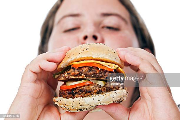 Towering cheeseburger on its way to plump woman's mouth