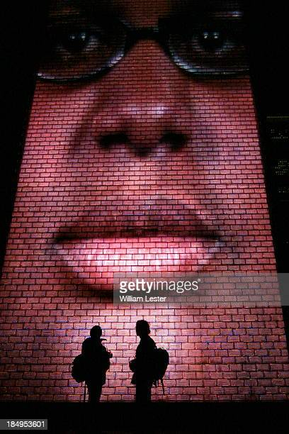 CONTENT] A towering figure looms over a pair of silhouetted men at the Crown Fountain Millennium Park in Chicago Illinois USA
