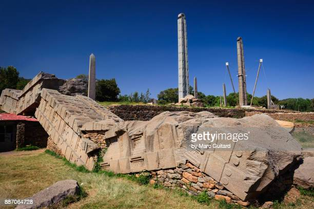 towering obelisks rising above one that was toppled at some point in the past. axum stelae park, axum, ethiopia - axum stock photos and pictures