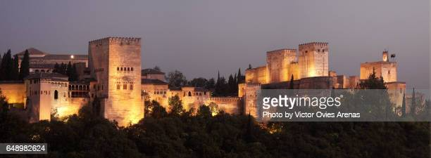 Towers and ramparts of the Alcazaba and the Alhambra illuminated at night from the Sacromonte viewpoint in Granada, Andalusia, Spain