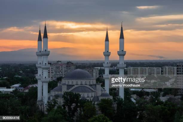 towers in cityscape at sunset - bisjkek stockfoto's en -beelden