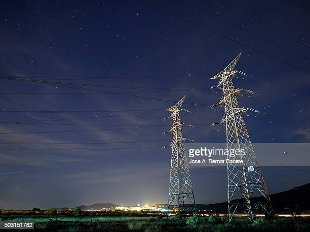 Towers of high tension in the night.