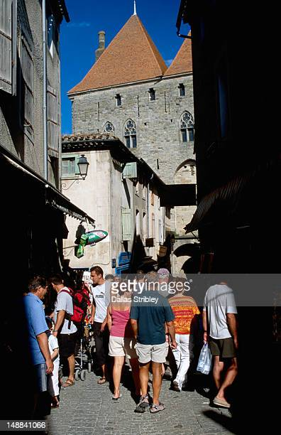 towers of porte narbonnaise over tourists wandering narrow streets of medieval walled city. - guy carcassonne photos et images de collection