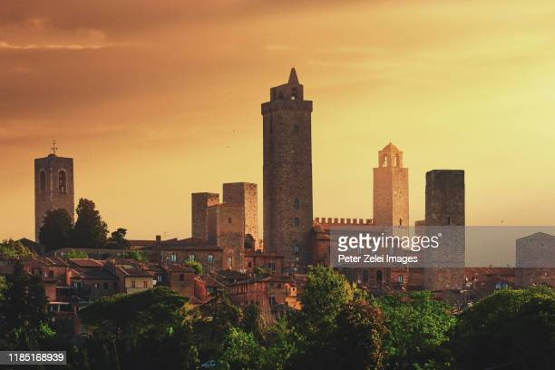 towers of san gimignano in tuscany, italy at sunset - サンジミニャーノ ストックフォトと画像