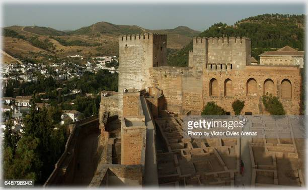 Towers of the Alcazaba and towers of the Alhambra at sunset with the Sacromonte and the Albaicin neighbourhoods in the background in Granada, Andalusia, Spain
