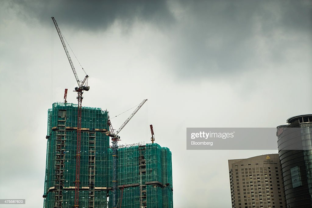 Towers stand under construction in Kuala Lumpur, Malaysia, on Wednesday, May 27, 2015. Malaysia's ringgit fell for a sixth day on June 1, in the longest stretch of losses since 2013 as falling oil prices weigh on the nation's finances. Photographer: Sanjit Das/Bloomberg via Getty Images
