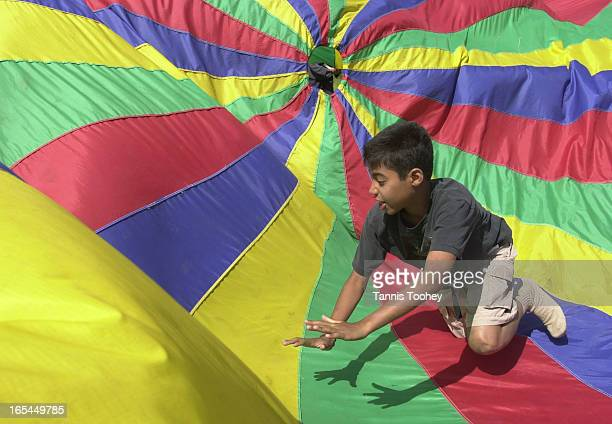 July 10 2001John plays the part of the cat as he chases the 'mouse' beneath the parachute during a game of cat and mouse at Camp Towhee in Haliburton