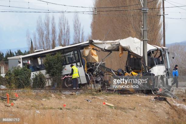 TOPSHOT A towing service worker and a gendarme walk next to the wreckage of school bus in Millas near Perpignan southern France on December 15 a day...