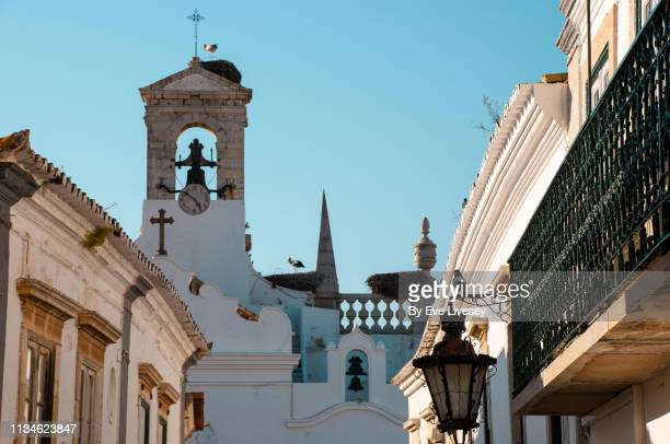 town arch & residential buildings in faro - faro city portugal stock photos and pictures