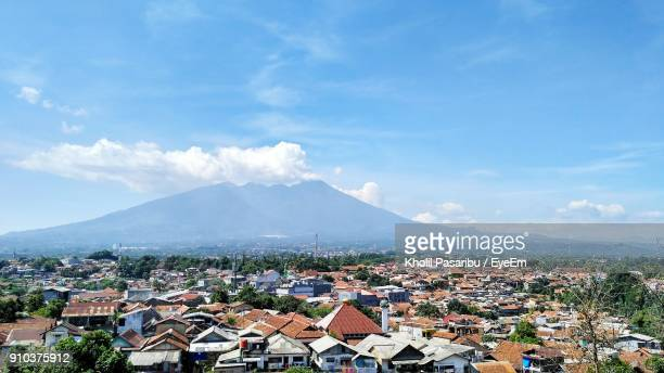 town by mountains against blue sky - bogor stock pictures, royalty-free photos & images