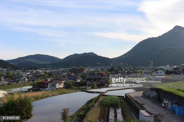 Town By River And Mountains Against Sky