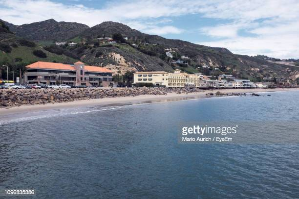 town by sea against sky - malibu beach stock pictures, royalty-free photos & images