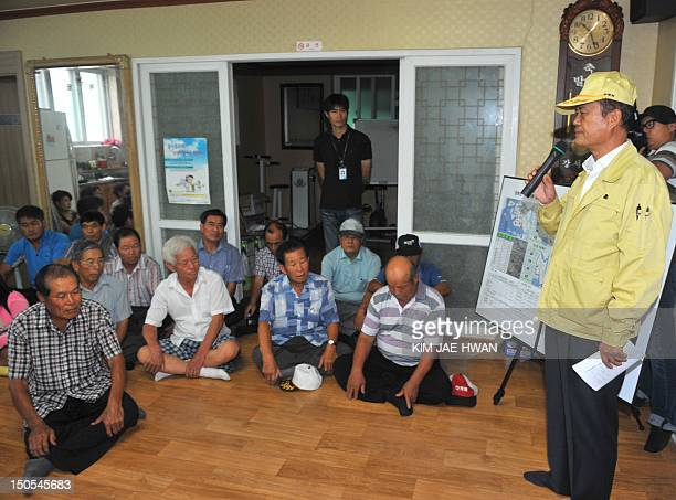 Town chief Bang MyongIk wearing a yellow cap and jacket briefs people in his frontline village during an evacuation drill on the western island of...