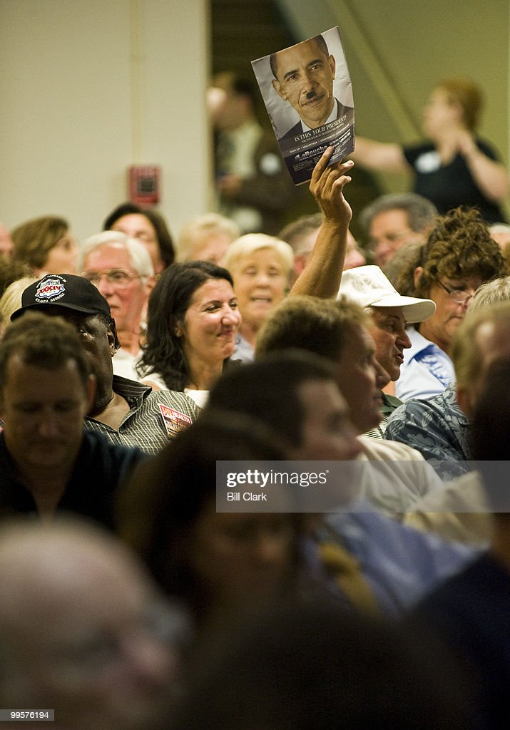 A town hall meeting attendee holds up a LaRouche publication featuring President Obama with a 'Hitler' mustache during Rep. Frank Pallone's town hall meeting at Red Bank Middle School in Red Bank, N.j., on Tuesday evening, Aug. 25, 2009.