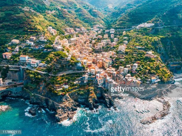 città in montagna che sovrasta il mare tranquillo, cinque terre, italia - liguria foto e immagini stock