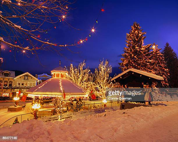 town, in snow,  decorated with holiday lights. - leavenworth washington stock photos and pictures
