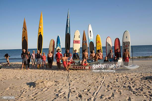 Town lifeguards surfers and paddleboarders line up at the beach for a photo before an annual charity swim to raise money in honor of a local woman...