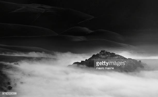 town on hill surrounded by fog, castelluccio, umbria, italy - カステッルッチョ ストックフォトと画像