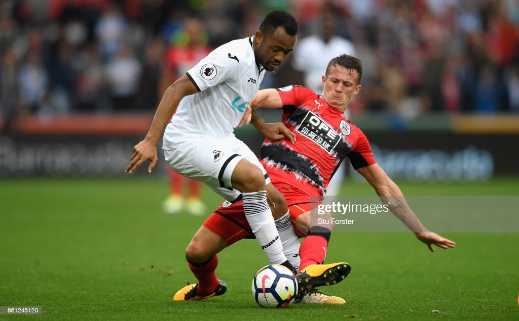 Town player Jonathan Hogg fouls Jordan Ayew of Swansea and receives a yellow card for it during the Premier League match between Swansea City and Huddersfield Town at Liberty Stadium on October 14, 2017 in Swansea, Wales.