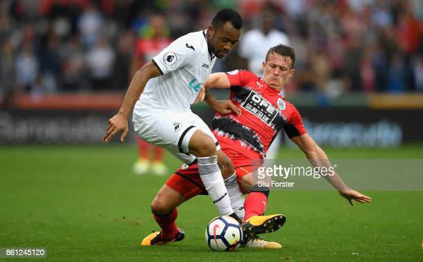 Town player Jonathan Hogg fouls Jordan Ayew of Swansea and receives a yellow card for it during the Premier League match between Swansea City and...