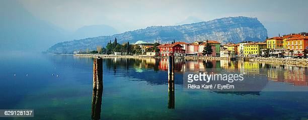 town reflection in lake garda against sky - lake garda stock pictures, royalty-free photos & images
